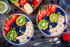 Breakfast bowl: oatmeal with banana, kiwi, strawberry, blueberries and chia seeds stock image