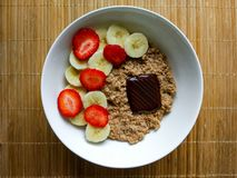 Breakfast bowl with strawberries and banana, with cereals and an ounce of dark chocolate royalty free stock photo