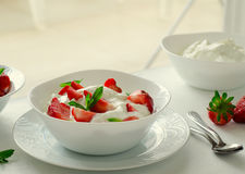 Breakfast with bowl of thick organic greek yogurt and fresh strawberries on white background. Toned Royalty Free Stock Photo