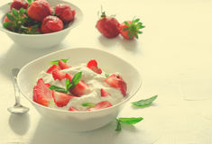 Breakfast with bowl of thick organic greek yogurt and fresh strawberries on white background. Toned Stock Photography