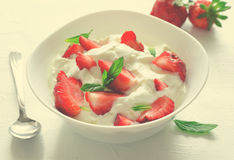 Breakfast with bowl of thick organic greek yogurt and fresh strawberries on white background. Toned Stock Photos
