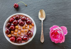 Breakfast bowl with yogurt,  granola or muesli or oat flakes, fresh cherries and nuts. Black stone background, pink rose flower. T Royalty Free Stock Photo