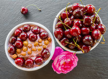 Breakfast bowl with yogurt,  granola or muesli or oat flakes, fresh cherries and nuts. Black stone background, pink rose flower Royalty Free Stock Image
