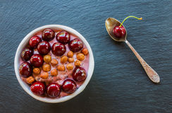 Breakfast bowl with yogurt,  granola or muesli or oat flakes, fresh cherries and nuts. Black stone background, top view Royalty Free Stock Images