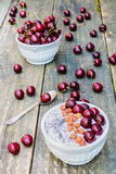 Breakfast bowl with yogurt, granola or muesli or oat flakes, fresh cherries and nuts. Old vintage wooden background and retro spoo Stock Photography