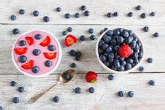 Breakfast bowl with yogurt, muesli, fresh blueberries and strawberries. Light wooden background, top view Royalty Free Stock Photography