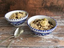 Breakfast bowls of stewed oats with banana and pistachios stock images