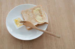 Breakfast. Bread and butter for breakfast on white plate on a wooden table Royalty Free Stock Images
