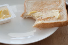 Breakfast. Bread and butter for breakfast on white plate on a wooden table Stock Photography