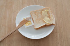 Breakfast. Bread and butter for breakfast on white plate on a wooden table Stock Photos