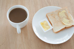 Breakfast. Bread and butter for breakfast on white plate on a wooden table Royalty Free Stock Photos
