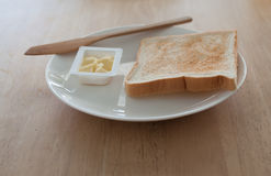 Breakfast. Bread and butter for breakfast on white plate on a wooden table Stock Images
