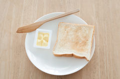 Breakfast. Bread and butter for breakfast on white plate on a wooden table Royalty Free Stock Photography