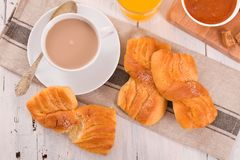 Breakfast with brioches. Breakfast with brioches on wooden table Royalty Free Stock Photography