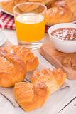 Breakfast with brioches. Breakfast with brioches on wooden table Royalty Free Stock Images