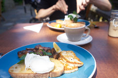 Breakfast / brunch. Breakfast or bunch of poached egg on toast, mushrooms and haloumi cheese royalty free stock photo