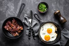Fried bacon and eggs. Breakfast or brunch fried bacon and eggs in black skillets and top view stock images