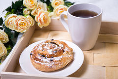 Breakfast with bun and tea on wooden tray. Close up of breakfast with bun and tea on wooden tray Royalty Free Stock Photos