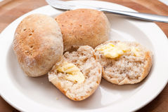 Breakfast buns. Fresh buns with butter on a plate for breakfast royalty free stock photography