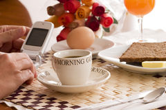 Breakfast business. Woman hands checking messages on the phone at brakfast time Royalty Free Stock Photo
