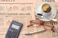 Breakfast and business. A financial newspaper with coffee cup stock image
