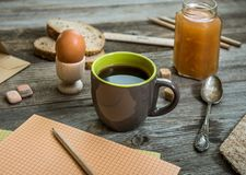 Breakfast business person. Coffee, sheets of notes and stationery on wooden table stock photo
