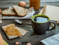 Breakfast business person. Coffee, sheets of notes and stationery on wooden table royalty free stock image