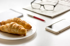 Breakfast for businessman with croissant on white table Royalty Free Stock Photography