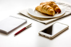 Breakfast for businessman with croissant on white table Stock Photos