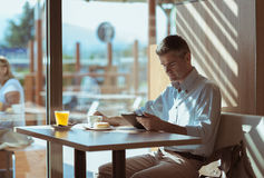 Breakfast at the cafe. Businessman having a delicious breakfast at the cafe, he is sitting at the table and using a touch screen tablet Stock Image