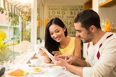 Breakfast at a cafe. Copy-spaced image of a young couple networking while having breakfast at a cafe Royalty Free Stock Images