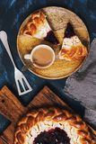 Breakfast, cake with cottage cheese and jam on a wood background. Pieces of cake and coffee on a wooden plate. View from above. Stock Photos