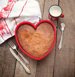 Breakfast cake inside heart baking tin over wood with vintage si Stock Photos