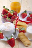 Breakfast with cappuccino, afternoon snack, strawberries and fruit juice. Cappuccino milk and fruit juice with strawberry and afternoon snack on wood of fir Royalty Free Stock Photos