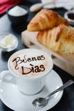 Breakfast cappuccino design - buenos dias. Cappuccino decorato e croissant breakfast Royalty Free Stock Photo