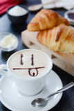 Breakfast cappuccino design - smile. Cappuccino decorato e croissant breakfast Royalty Free Stock Photography