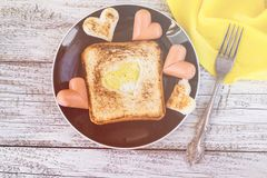 Breakfast for the celebration of Valentine day with sausage and eggs in the bread heart shaped.  royalty free stock photo