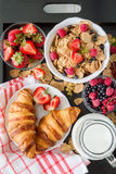 Breakfast - cereal and berries in white bowl, croissant Stock Images
