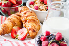 Breakfast - cereal and berries in white bowl, croissant Stock Image