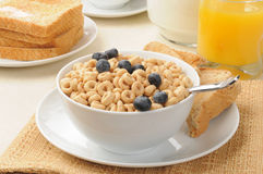 Breakfast cereal with blueberries and toast. A bowl of oat breakfast cereal with blueberries, toast and orange juice Stock Image