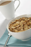 Breakfast cereal and coffee. A closeup tabletop view of a large bowl of dry breakfast cereal flakes and a cup of coffee stock photography