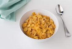 Breakfast cereal of cornflakes in bowl on white table. With spoon Stock Images