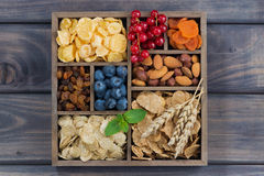 Breakfast cereal, dried fruit, berries and nuts in a wooden box Stock Image