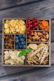 Breakfast cereal, dried fruit, berries and nuts in a wooden box Stock Photography