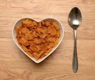 Breakfast cereal in heart shaped bowl. With spoon on wooden table Stock Images