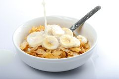 Breakfast Cereal and Milk. Bowl of corn flakes with sliced banana and milking pouring on top Stock Images