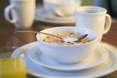 Breakfast cereal in the morning sun. Cereal and coffee for breakfast basking in the early morning warm sunlight royalty free stock photos