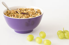 Breakfast Cereal in Purple Bowl with Grapes. Royalty Free Stock Photo