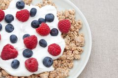 Breakfast cereal with raspberries & blueberries. Breakfast cereal with fresh raspberries, blueberries and yogurt in a dish Stock Images
