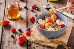 Breakfast cereal rustic with a hand swirling honey royalty free stock images